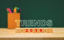 Tendances 2019 sur le cube en bois avec la boîte colorée de stylo sur la table en bois avec le mur vert de tableau noir futur con image libre de droits