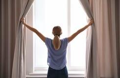 Tende di apertura della donna e guardare dalla finestra fotografie stock libere da diritti