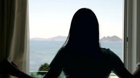 Tende di apertura della giovane donna in una camera da letto Vista del mare, delle palme e delle montagne attraverso la finestra video d archivio