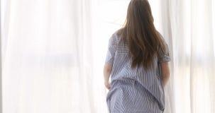 Tende di apertura felici della donna sulla finestra archivi video