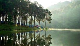 Tende di campeggio al campeggio all'aperto vicino al lago con luce solare a Fotografie Stock Libere da Diritti