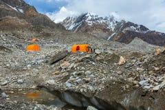 Tende di montagna arancio sul ghiacciaio gigante Immagine Stock