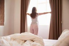 Tende facenti una pausa della finestra e di apertura della camera da letto della donna fotografia stock