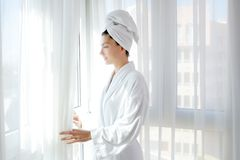 Tende piene di sole di bianco della finestra della donna dell'accappatoio Fotografia Stock Libera da Diritti