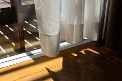Tende pure bianche con luce solare luminosa ed il pavimento di legno Immagine Stock
