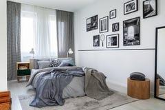 Tende a quadretti sulla finestra della camera da letto contemporanea interna con il comodino ed il letto a due piazze di legno co fotografie stock libere da diritti