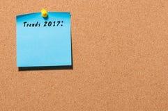 Tendencias 2017 escritas en la etiqueta engomada azul fijada en el tablón de anuncios del corcho con el espacio vacío para el tex Imágenes de archivo libres de regalías