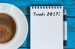 Tendencias 2017 escritas en la libreta en lugar de trabajo azul de la tabla cerca de la taza de café de la mañana Negocio y moda  Fotografía de archivo libre de regalías