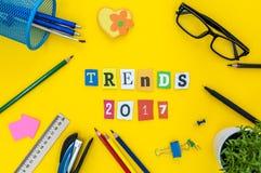 2017 tendencias - texto de letras talladas en el fondo amarillo de la tabla con las fuentes de la oficina o del alumno Foto de archivo libre de regalías