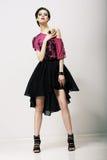 Tendency. Glamorous Fashion Model in Modern Clothes posing in Studio Stock Photo