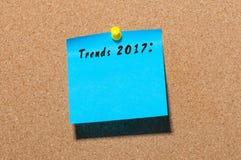 Tendensen 2017 geschreven op blauwe die sticker bij berichtraad wordt gespeld Nieuwe jaarzaken en manierinnovatie Stock Foto's