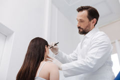 Tender admirable beautician using pencil for marking important areas Royalty Free Stock Photography