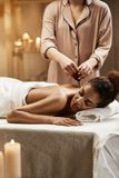 Tender african girl relaxing enjoying healthy spa massage with oil. Tender beautiful african girl relaxing enjoying healthy spa massage with oil Royalty Free Stock Photo