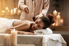 Tender african girl relaxing enjoying healthy spa massage with oil. Tender beautiful african girl relaxing enjoying healthy spa massage with oil Royalty Free Stock Photos