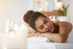 Tender african girl resting relaxing with closed eyes in spa salon. Stock Photos