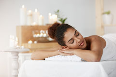 Tender african girl resting relaxing with closed eyes in spa salon. Stock Images