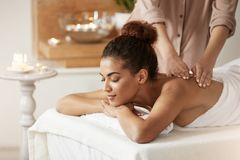 Tender african girl smiling enjoying massage with closed eyes in spa resort. Tender beautiful african girl smiling enjoying massage with closed eyes in spa Stock Photos
