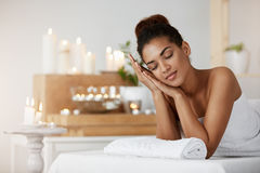 Tender african girl smiling resting relaxing with closed eyes in spa salon. Young tender african girl smiling resting relaxing with closed eyes in spa salon Stock Photos