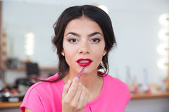 Tender attractive young woman putting on red lipstick Stock Images
