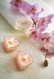 Tender bath accessories. Pink candles, perfumed salt, white towel with tender orchids around Stock Photo