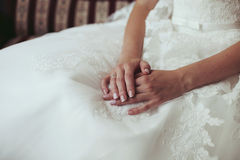 Tender beautiful bride's hands on elegant white wedding dress cl Stock Photo