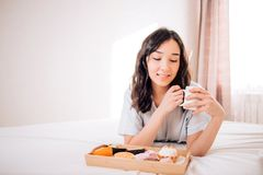 Young woman eating healthy breakfast in bed. Tender beautiful caucasian girl in pajamas smiling looking away resting relaxing at home. Amazing joyful brunette stock photos