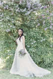 Tender beautiful cute girl bride in a white air dress with a bouquet of lilacs in her hands walking through the park on a sunny sp. Ring day. Photo in gentle Royalty Free Stock Photo