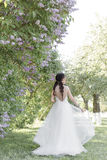 Tender beautiful cute girl bride in a white air dress with a bouquet of lilacs in her hands walking through the park on a sunny sp Stock Photography