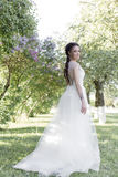 Tender beautiful cute girl bride in a white air dress with a bouquet of lilacs in her hands walking through the park on a sunny sp Stock Image