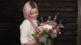 Tender, beautiful girl whirls with flowers in hands, enjoying the beauty of a bouquet. Dark background.  stock footage
