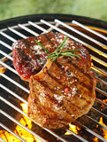Tender beef steaks grilling over the flames royalty free stock images