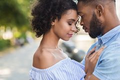Tender black couple bonding to each other. And touching foreheads on the street royalty free stock images
