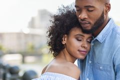 Tender black couple hugging with closed eyes. Outdoors royalty free stock photos