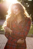 Tender blonde model in checkered dress posing in rays of sun at stock image