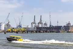 A tender boat of the SS Rotterdam with in the background the cranes in the Waalhaven of Rotterdam transports passengers to and fro. M the hotel ship royalty free stock photo