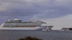 Tender boats are sailing aside of Voyager of the Seas large cruise ship stock video