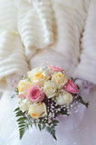 Tender bouquet in hands of bride. Delicate bouquet with beige and pink roses in hands of bride Stock Photo
