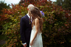 Tender bride stands behind a groom with closed eyes in the front Royalty Free Stock Image