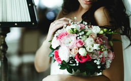 Tender bride touches a pink wedding bouquet standing in the hotel.  royalty free stock photography