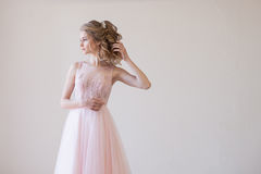Tender bride in a white room before the wedding. In pink dress Royalty Free Stock Images