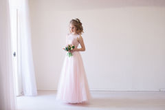 Tender bride in a white room before the wedding. In pink dress Royalty Free Stock Image