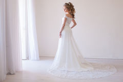 Tender bride in a white room before the wedding stock images