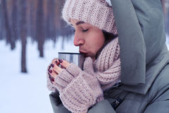 Tender calm young woman tasting tea from cup in a snowy forest Stock Photo