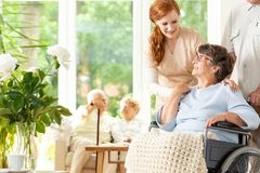 Tender caregiver saying goodbye to an elderly pensioner in a wheelchair in a day care facility. A companion pushing. The wheelchair. Other elderly people in the royalty free stock image
