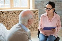 Tender caregiver taking participation in senior mans life. Health monitoring. Appealing skillful caregiver carrying clipboard while wearing glasses and stock images