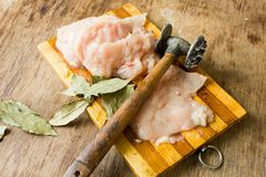 Tender chicken fillet and hammer for meat Royalty Free Stock Photos