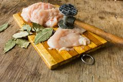 Tender chicken fillet and hammer for meat. Tender chicken fillet knife hammer for beating the meat and bay leaves on the wooden table Stock Photos