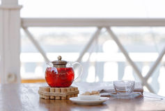 A hot beverage from juicy strawberries and red currant on a blurred white background. A beautiful tea composition. Copy. A tender composition of a transparent Stock Images