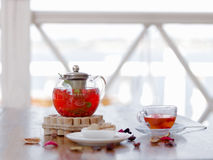 A hot beverage from juicy strawberries and red currant on a table and on a blurred background. Traditional tea ceremony. A tender composition of a transparent Royalty Free Stock Photos