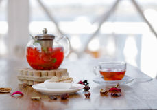 A hot beverage from juicy strawberries and red currant on a table and on a blurred background. Traditional tea ceremony. A tender composition of a transparent Stock Photography